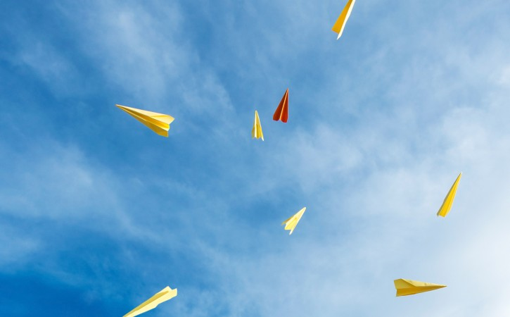 yellow and orange aircraft rocket paper hand made floating in the blue sky